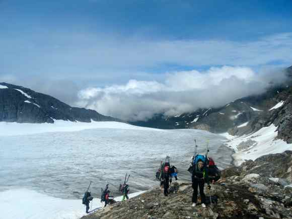 Hiking over rocks with the Lemon Creek Glacier ablation zone in the background