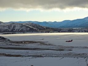 A small plane lands on the runway above the frozen delta