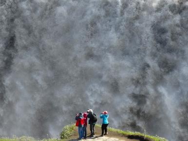 Tourists enjoying Dettifoss, the most powerful waterfall in Europe